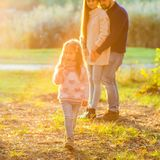 Family playing in autumn park having fun at sunset. Park at sunset of the day Royalty Free Stock Photography