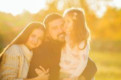 Family playing in autumn park having fun at sunset. Girl playing at sunset in park with parents Royalty Free Stock Image