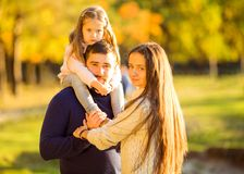 Family playing in autumn park having fun at sunset. Park at sunset of the day Stock Photos
