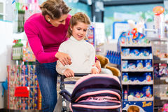 Family playing with baby doll carriage in toy store Royalty Free Stock Photo
