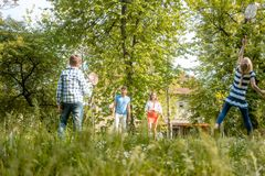 Family playing badminton on a meadow in summer Stock Images