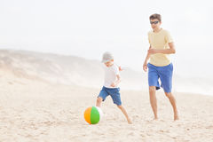 Family playing with ball at the beach Stock Photos