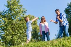 Family playing ball on summer meadow Stock Images