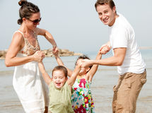 Family playing on the beach. Young couple embracing and enjoying with two young children in beach stock photos