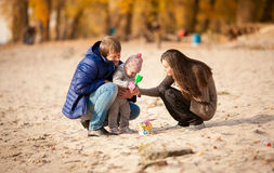 Family playing on beach with daughter at autumn Stock Image