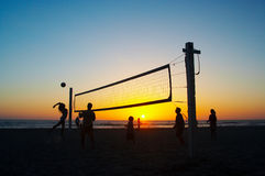 Family playing beach volleyball. In the evening Stock Photography