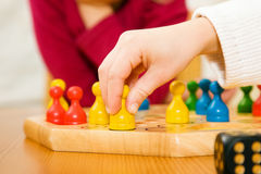 Family playing a board game. Child is moving a piece, a dice is to be seen royalty free stock photography