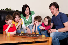 Family is playing an board game Royalty Free Stock Photos