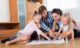 Family playing at board game. American family of four playing at board game in domestic interior stock image