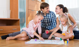 Family playing at board game. Family of four playing at board game in domestic interior stock photo