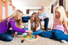 Family playing board game at home. Family playing board game ludo at home on the floor stock image