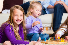 Family playing board game at home. Family playing board game ludo at home on the floor stock photo