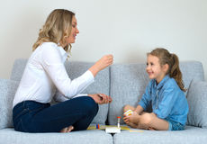 Family playing board game. Mother and daughter playing board game at home Stock Image
