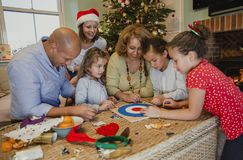Playing Board Games At Christmas. Family are playing board games together in the living room of their home at christmas time Royalty Free Stock Images