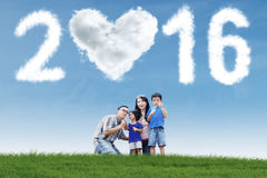 Family playing bubble at field with numbers 2016 Stock Images