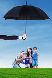 Family playing bubble at field under umbrella. Portrait of happy family playing bubble on the meadow under umbrella. Life and family insurance concept Stock Images