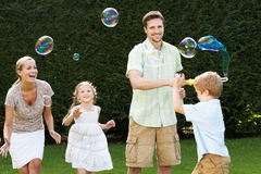 Family Playing With Bubbles In Garden Royalty Free Stock Image