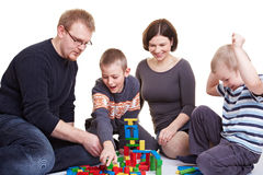 Family playing with building bricks. Happy family with two children playing together with building bricks royalty free stock photo
