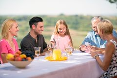 Family playing cards outdoors stock photography