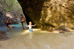 A family playing in a cave at a beach in the tropics Royalty Free Stock Images