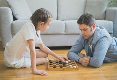 Family playing checkers. Royalty Free Stock Photos