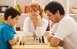 Family playing chess. Father and his son playing chess meantime the young beautiful woman smiling royalty free stock photo