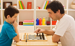 Family playing chess. Father showing to his son the first steps of the chess Stock Image