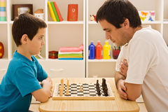 Family playing chess. Father and his son playing chess royalty free stock photos