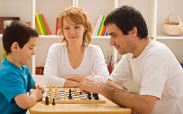 Family playing chess. Father and his son playing chess meantime the young beautiful woman smiling stock photography