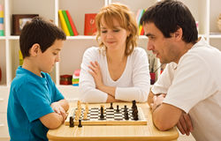Family playing chess. Father and his son playing chess meantime the young beautiful woman smiling stock image