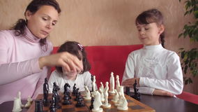 Family playing chess. Family playing chess at home on a red couch. Full hd stock video footage