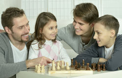 Family playing chess at home Stock Image
