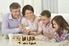 Family playing chess. Portrait of a happy family playing chess at home royalty free stock image
