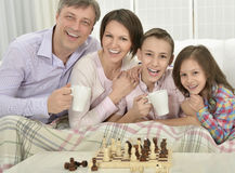 Family playing chess. Portrait of a happy family playing chess at home royalty free stock images