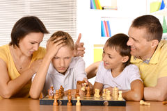 Family playing chess sitting at table Stock Photography