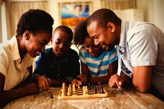 Family playing chess together at home in the living room stock image