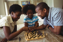 Family playing chess together at home in the living room. At home Stock Image