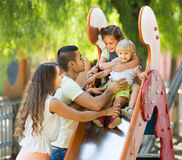 Family playing at children's slide Royalty Free Stock Images