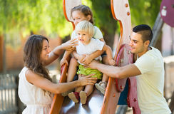 Family playing at children's slide Royalty Free Stock Photography
