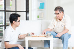 Family Playing Chinese Chess. Chinese family playing Chinese chess (Xiang Qi) at home, senior father and adult son Stock Photos
