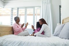 Family playing clapping games on bed in bedroom Royalty Free Stock Photography