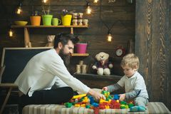 Family playing with constructor at home. Dad and child play with toy cars, bricks. Father and happy son play with royalty free stock photos