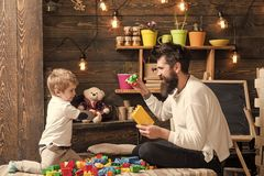 Family playing with constructor at home. Dad and child play with toy cars, bricks. Nursery with toys and chalkboard on. Background. Father and happy son play royalty free stock photography