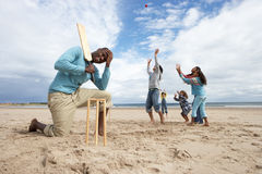 Family playing cricket on beach. Having fun stock photography