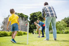 Family playing cricket in park Stock Photo