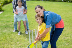 Family playing cricket in park Stock Image