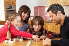 Family Playing Dominoes In Kitchen. Having Fun Stock Photo