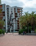Family playing and feeding pidgeons next to sculpture in Barcelona stock image