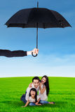 Family playing at field and protected by umbrella Royalty Free Stock Images