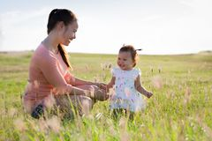 Family playing in the fields on top of a grassy hill having a good time. Mother and daughter laughing and playing on a sunny day in a field outdoor Royalty Free Stock Photos